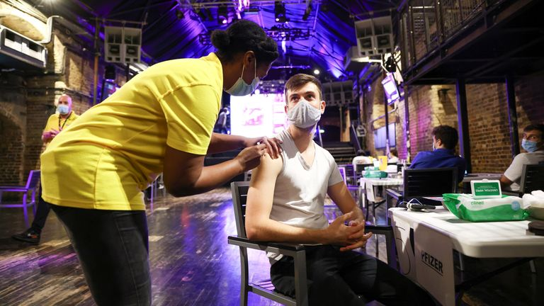 A person receives a dose of the Pfizer BioNTech vaccine at an NHS vaccination centre hosted at the Heaven nightclub, amid the coronavirus disease (COVID-19) pandemic, in London