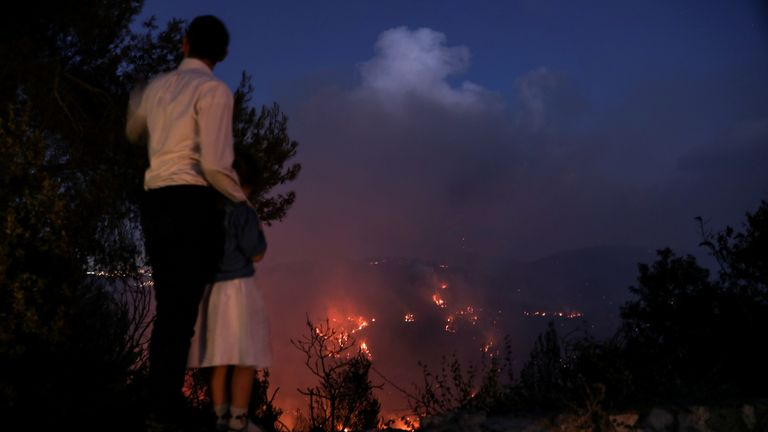 A man and his daughter watch as wildfire burns on the opposite mountain near Shoeva, on the outskirts of Jerusalem