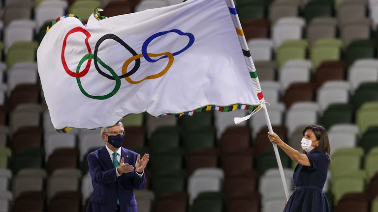 Paris Mayor Anne Hidalgo waves the Olympic flag after receiving it from International Olympic Committee's President Thomas Bach during the closing ceremony in the Olympic Stadium at the 2020 Summer Olympics, Sunday, Aug. 8, 2021, in Tokyo, Japan. (Dan Mullen/Pool Photo via AP))