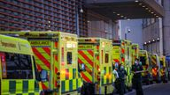 NHS workers walk next to a cue of ambulances outside the Royal London Hospital, in London, Britain January 12, 2021. REUTERS/Henry Nicholls