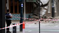 A police officer closes an intersection where debris is scattered in the road after an earthquake damaged a building in Melbourne, Wednesday, Sept. 22, 2021. A magnitude 5.8 earthquake caused damage in the city of Melbourne in an unusually powerful temblor for Australia, Geoscience Australia said. (James Ross/AAP Image via AP)