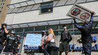 Protesters hold signs during an anti-vaccine mandate protest outside Toronto General Hospital in Toronto