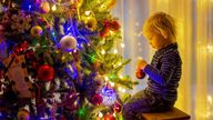 blonde toddler boy, decorating christmas tree with balls and light strings at home PIC:ALAMY