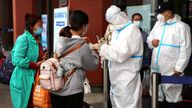 People outside a rail station in China are checked for proof of negative COVID tests