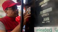 A gas station worker tries to set the new gasoline price after the latest increase in fuel prices, with most meters unable to accommodate the new five digit price for one liter of gas, in Beirut, Lebanon, Wednesday, Sept. 22, 2021.