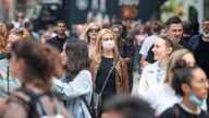 A woman wears a face mask among a crowd of pedestrians on Oxford Street, London