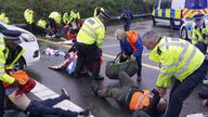 Police officers detain a protester from Insulate Britain occupying a roundabout leading from the M25 motorway to Heathrow Airport in London.