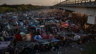 Migrants take shelter along the Del Rio International Bridge at sunset as they await to be processed after crossing the Rio Grande river into the U.S. from Ciudad Acuna in Del Rio, Texas, U.S. September 19, 2021. Picture taken with a drone. REUTERS/Adrees Latif TPX IMAGES OF THE DAY