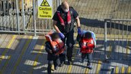 A Border Force officer helps young children brought in to Dover, Kent, with a group of people thought to be migrants following a small boat incident in the Channel. Picture date: Wednesday September 8, 2021.