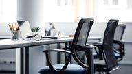 Modern gadgets in interior of coworking office during COVID-19 epidemic. Chairs and desk for support workers, laptops and headphones, cups and stationery in daylight on window background, free space