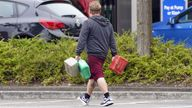 A man carrying containers at a petrol station in Bracknell, Berkshire