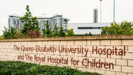 Glasgow, Scotland - A sign at the entrance to the Queen Elizabeth Hospital in Govan, Glasgow, with the main hospital building in the distance.