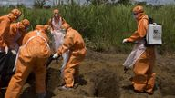 A burial team wearing protective clothes prepares an Ebola virus victim for interment, in Port Loko, Sierra Leone, September 27, 2014