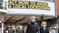 People wearing face masks walk past a advertisement on Market Street in Manchester, as the city is waiting to find out if the region will be placed into the Very High category with tier 3 lockdown restrictions to curb the spread of coronavirus.