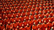 Personnel in orange hazmat suits march during a paramilitary parade held to mark the 73rd founding anniversary of the republic at Kim Il Sung square in Pyongyang in this undated image supplied by North Korea's Korean Central News Agency on September 9, 2021. KCNA via REUTERS