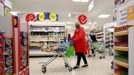 A woman wearing a face mask pushes a shopping cart at a Tesco supermarket in Hatfield, Britain October 6, 2020