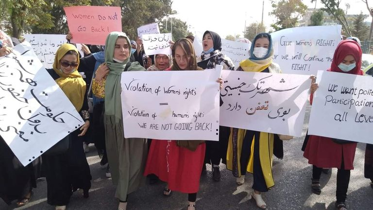 Women hold banners as they attend a demonstration in Mazar-e-Sharif, Afghanistan
