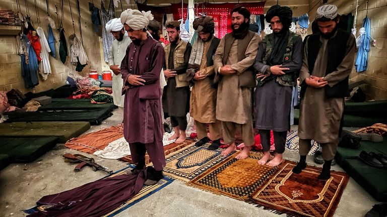 Taliban fighters pray inside the cells