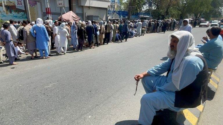 Afghans line up outside a bank to take out their money after Taliban takeover in Kabul