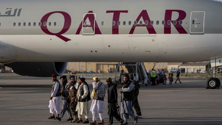 Taliban fighters walk past the flight at the airport in Kabul. Pic: AP