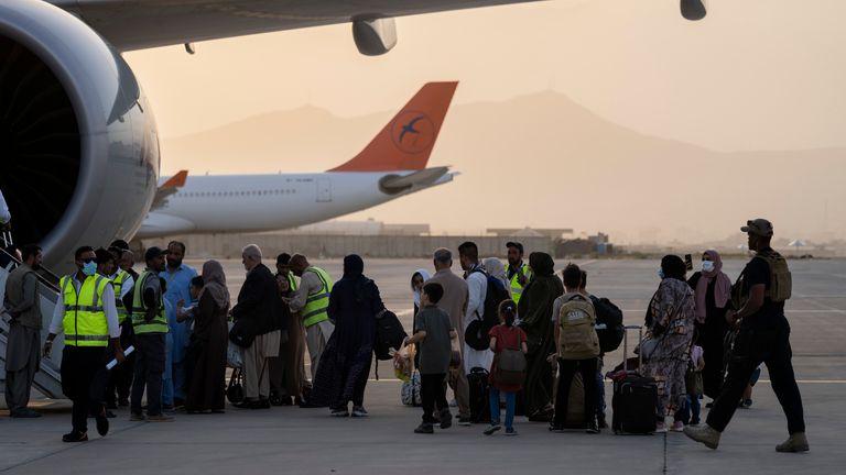 People board the Qatar Airways flight to Doha. Pic: AP