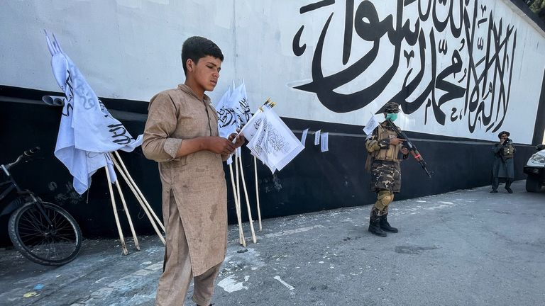 A young boy sells Taliban flags in front of the US embassy