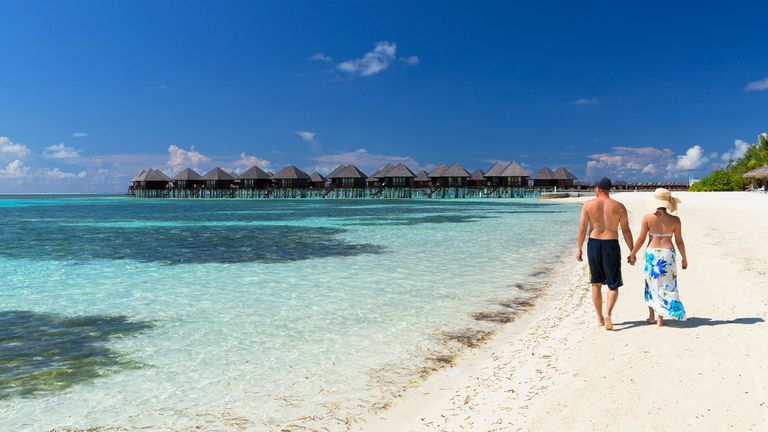 Couple on beach at Olhuveli Beach and Spa Resort, South Male Atoll, Kaafu Atoll, Maldives -