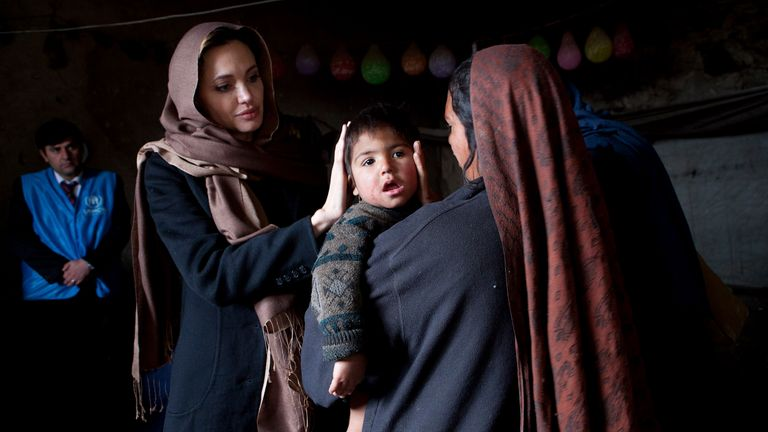 Jolie meets a family at their makeshift home near Kabul in 2011