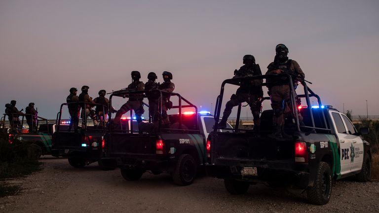 Mexican police stand guard near the Rio Grande river in Ciudad Acuna, Mexico PIC:AP