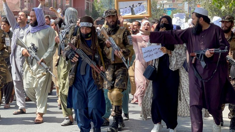Taliban forces walk in front of Afghan demonstrators as they shout slogans during an anti-Pakistan protest, near the Pakistan embassy in Kabul, Afghanistan