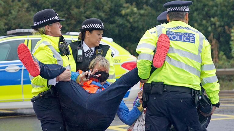 Police officers detain protesters from Insulate Britain occupying a roundabout leading from the M25 motorway to Heathrow Airport in London.