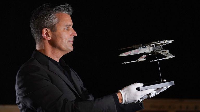 Stephen Lane, directeur général de Prop Store, brandit la miniature de tournage X-wing lumineuse de Star Wars: Return of the Jedi, avant la vente aux enchères