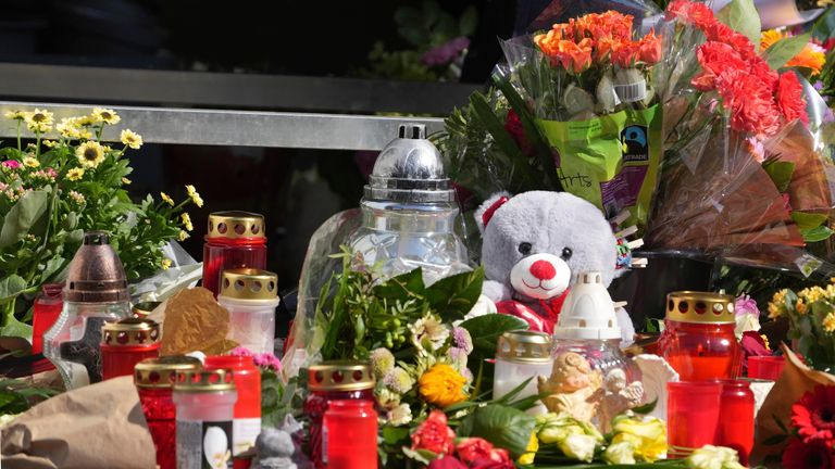 Flowers, candles and messages to the victim lie at a gas station downtown. An employee of the gas station had been shot by a man armed with a pistol on Saturday evening. The clerk had advised the suspect that masks were mandatory because the man wanted to buy beer without a mask. Later, the man returned and shot the victim. PIC:AP