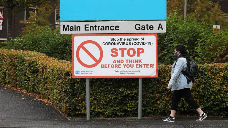 A woman wearing a face mask walks past an entrance to Belfast City Hospital