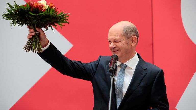 Social Democratic Party (SPD) leader and top candidate for chancellor Olaf Scholz holds a bouquet of flowers at their party leadership meeting, one day after the German general elections, in Berlin, Germany,