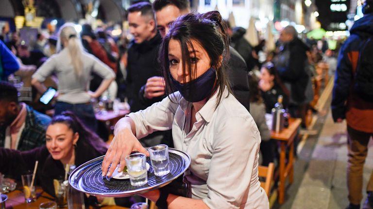 """Une serveuse sert des boissons à des tables d'installation à l'extérieur des pubs de Soho, à Londres, le jour où certaines des troisièmes restrictions de verrouillage des coronavirus en Angleterre ont été assouplies par le gouvernement britannique, le lundi 12 avril 2021. Les gens de toute l'Angleterre ont afflué pour se débarrasser des poils hirsutes serrures et recherchez des vêtements, des livres et d'autres """"non essentiel"""" des articles comme les magasins, les gymnases, les coiffeurs, les terrasses de restaurants et les jardins à bière ont rouvert lundi après des mois de verrouillage.  (Photo AP/Alberto Pezzali)"""