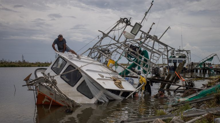 James Serigny climbs atop his sunken shrimp boat while getting help from friends to raise it, in the aftermath of Hurricane Ida in Golden Meadow, Louisiana,