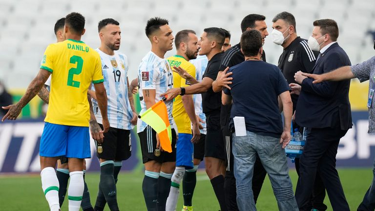 Brazil and Argentina players talk as the game is interrupted by health officials. Pic: AP