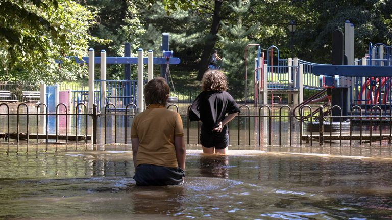 Tiger Lily Koch, 10, is pictured with her brother, Adrien at a flooded playground after the remnants of Tropical Storm Ida brought drenching rain and the threat of flash floods and tornadoes to parts of the northern mid-Atlantic, in the Brooklyn borough of New York City, U.S., September 2, 2021. REUTERS/Caitlin Ochs