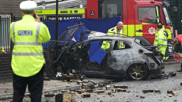The burnt out shell of a car at the scene on the Great Western Road, Notting Hill, west London, where three people have died after the vehicle collided with a residential block. Picture date: Tuesday September 14, 2021.