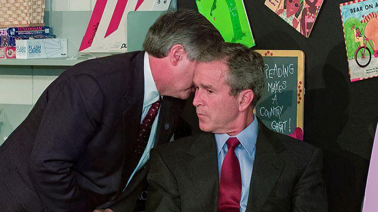 White House chief of staff Andrew Card whispers into the ear of President George W Bush