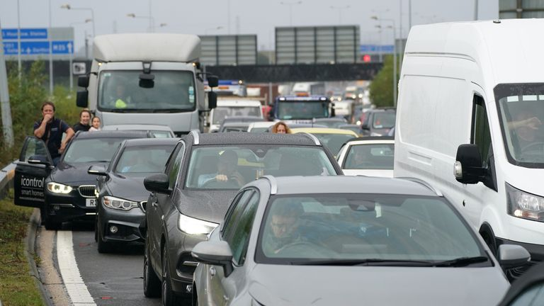 Drivers stand watching from their cars as traffic is halted during a roadblock by protesters from Insulate Britain at a roundabout leading from the M25 motorway to Heathrow Airport in London.