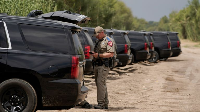 A Texas Department of Safety official stands near a line of vehicles along a road adjacent to the Rio Grande, Tuesday, Sept. 21, 2021, in Del Rio, Texas. The U.S. is flying Haitians camped in a Texas border town back to their homeland and blocking others from crossing the border from Mexico.  PIC:AP