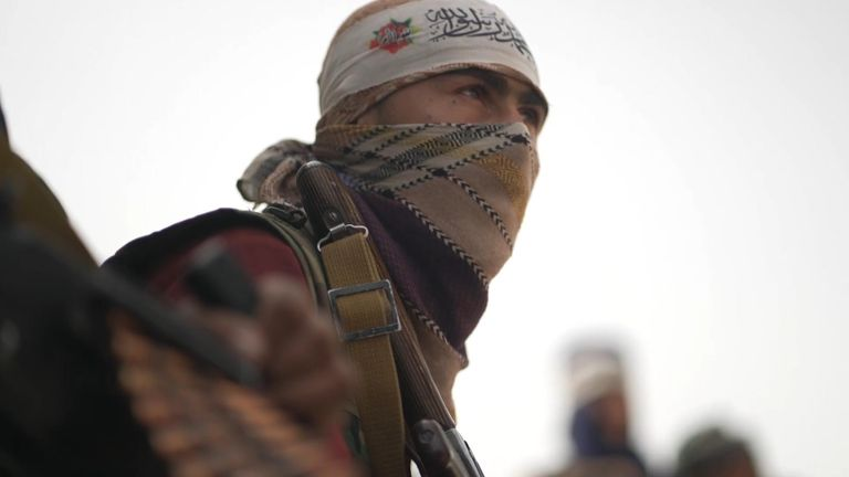 An armed Taliban fighter looks on