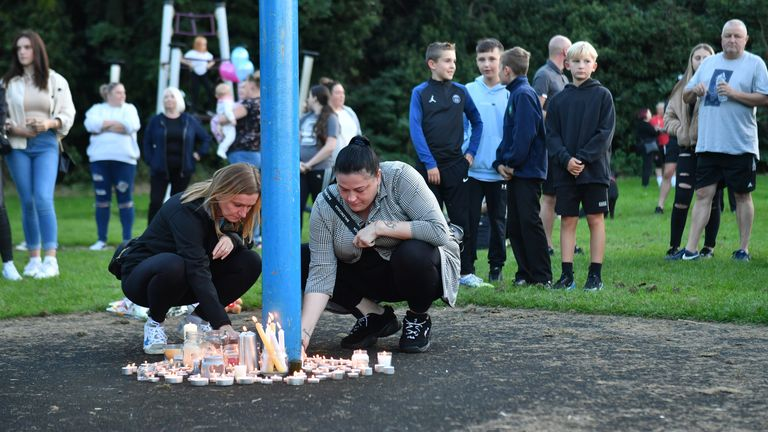 Members of the public light candles as they attend a vigil near to the scene in Chandos Crescent, Killamarsh