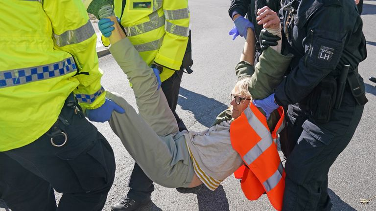 Police officers carry away a protester from Insulate Britain