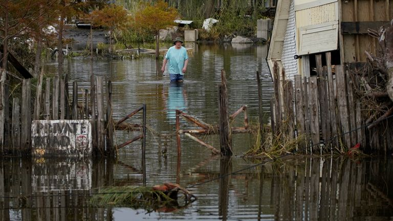A man walks down a flooded street in the aftermath of Hurricane Ida - Picture date 1 August PIC:AP
