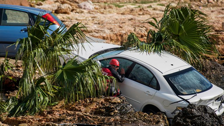 A firefighter checks a wrecked car stuck in the shore of the seaside town of Alcanar, in northeastern Spain, Thursday, Sept. 2, 2021 PIC:AP