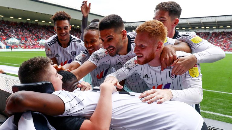 Fulham players celebrate the opening goal with fan Rhys Porter. Pic: Rex Features/Shutterstock