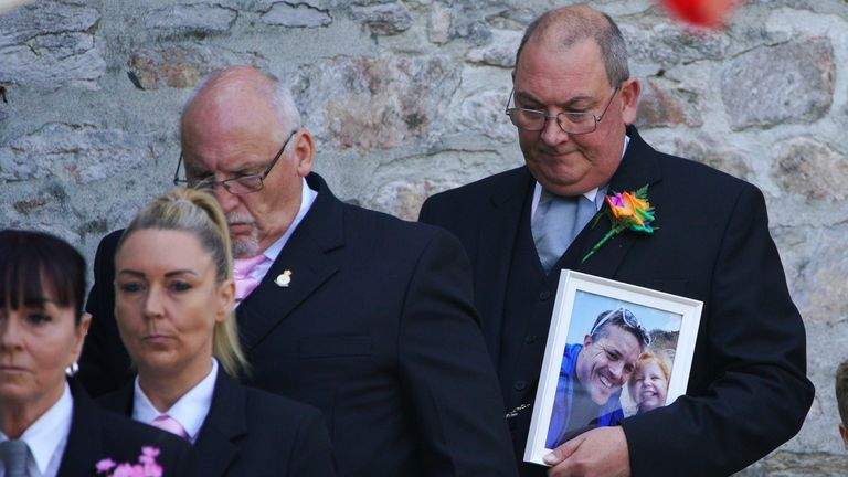 A man carries a photograph of the victims of the Plymouth shootings three-year-old Sophie Martyn and her father Lee Martyn, 43, from the Church of St Andrews, Plymouth, as the cortege leaves following their funeral. Picture date: Monday September 6, 2021.